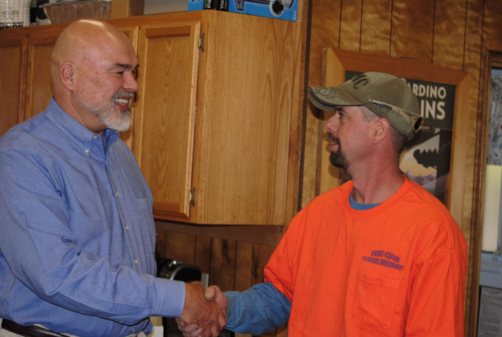 PCWD PROMOTION: Mike Esnard (left), Pine Cove Water District board president, congratulates Jeremy Potter (right) after his promotion to field foreman, following the resignation of Jerry Johnson.      Photo by J.P. Crumrine