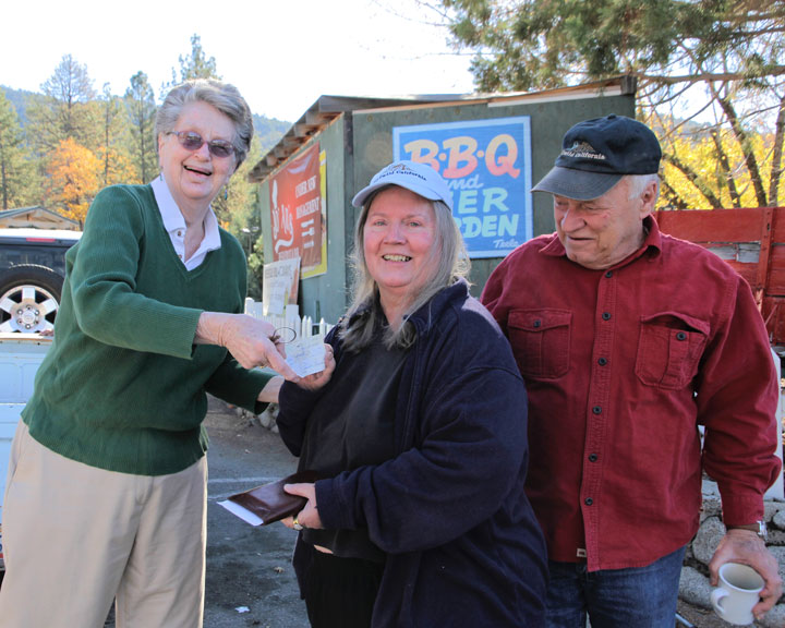 Judy Begin (left) of the Idyllwild Gift Shop, hands to Phyllis Mueller, one of the top dogs of the Tree Lighting Ceremony executive team, a donation to save the Christmas tree that is threatened by the drought, while Joe McNabb, who assisted with mounting the lights, looks on Saturday.Photo by John Drake