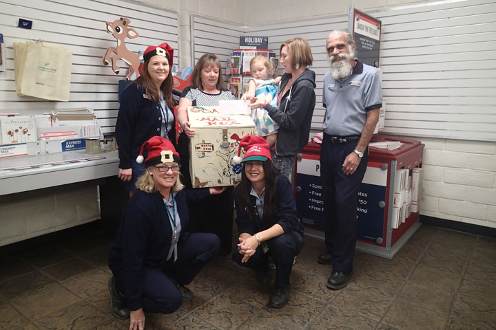NORTH POLE MAIL: Evelyn Teel, 3, is the first to drop her letter to Santa in the North Pole-bound mail box at the Idyllwild Post Office. Helping Santa are post office employees Julie Stanford and Christina Reitz (front), Kelsi Lehman, Postmaster Kelly Gates, Mom Theresa Teel and John Aussenhofer. The mail box will be in the Idyllwild Post Office lobby until Friday, Dec. 12, for children to send Santa their Christmas wishes.Santa allows the Town Crier to print the letters in the Christmas edition for readers to enjoy. Photo by Halie Wilson