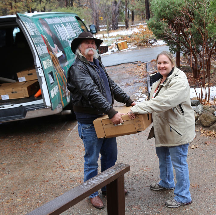 TURKEY OFFERING: Colleen Meyer (right) of the Idyllwild HELP Center accepts a donation of 30 Christmas turkeys from the Idyllwild Arts Foundation.       Photo by Joanne Bischof