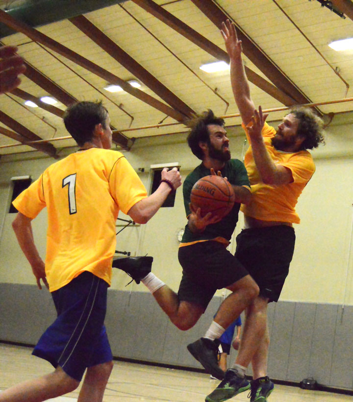 ADULT BASKETBALL: Brian Ensman (center) of Lee's Green Giants, heads for the hoop in Town Hall adult 3-on-3 basketball at Idyllwild gym Wednesday evening, Dec. 3. Blake Swanson (left) and Scott Alton (right) of Dora's Yellow Jackets attempt to block the shot. Lee's Green Giants went home with the win.           Photo by Gallagher Goodland