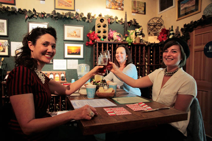 Cheers from locals Alicia Provenzano (left), Kirby Urtiaga (right) and Joyce Simanek as the friends enjoy the beers at Idyll Awhile's Christmas Beer Tasting last week. Photo by John Drake