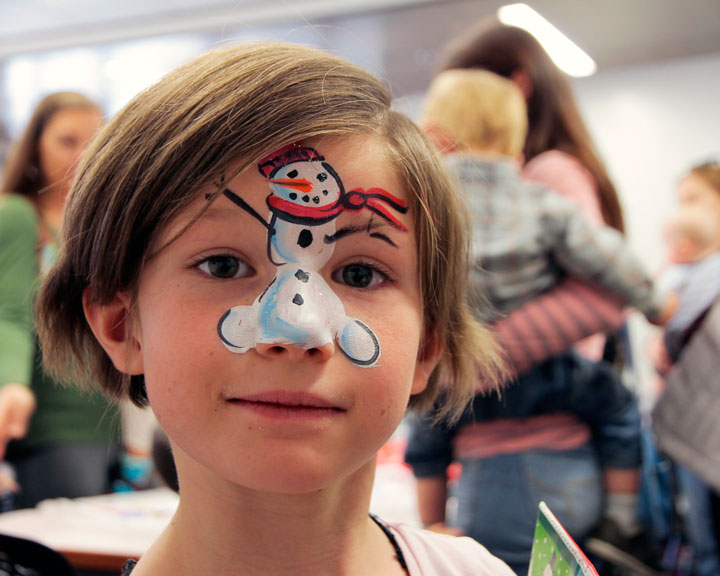 NO SCHOOL, BUT PLENTY TO DO: Samantha Hoggan shows off her holiday face painting courtesy of Mrs. Claus who visited the library Monday morning. Photo by John Drake