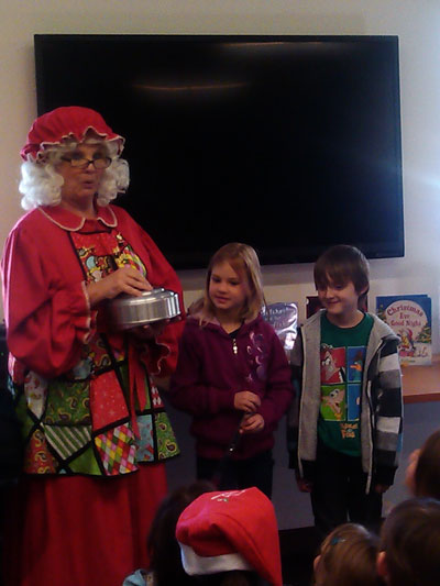 """SPECIAL HOLIDAY STORY TIME: Mrs. Claus and """"elves"""" Rylan Righetti and Carter Johnson help with a magic trick at Idyllwild Library's storytime on Monday. Photo by Wendy Watts"""