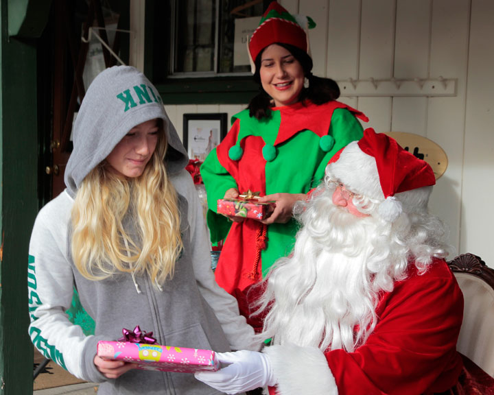 Phoebe Sandal receives a gift and a picture with Santa at New Spirit Vacation Homes' Toy Drive giveaway on Sunday. Photo by John Drake