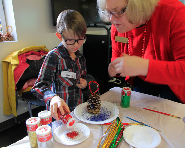 CHRISTMAS WORKSHOP: Susan Righetti helps Nicholas Salesky with the glitter during the Christmas Present Workshop at Idyllwild Library on Saturday.        Photo by John Drake