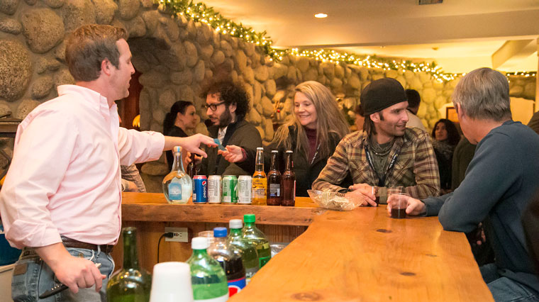 Tuesday night kicked off the 2015 Idyllwild International Festival of Cinema. Betty Baily, center, hands her drink ticket to Mark Croudy behind the bar during the opening night party at the Creekstone Inn. Photo by Jenny   Kirchner