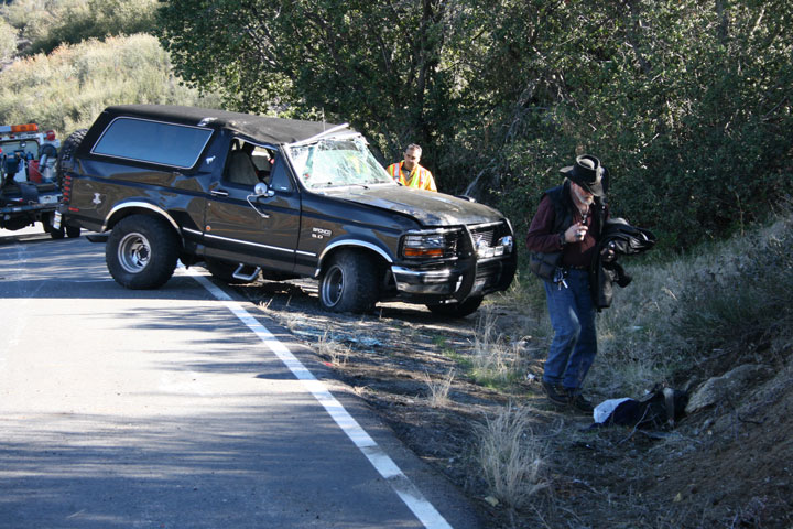 """Above, this crash was reported around 11:17 a.m. Monday involving a pick-up truck with a camper shell driven by Leif Kvammen (right) of Pine Cove. Kvammen was not injured and no other vehicles or persons were involved in the collision. Kvammen, traveling westbound on Highway 74 near the Strawberry Creek Bridge, said he heard a """"pop and clash"""" at the same time coming from his right front wheel, immediately dragging the vehicle off the pavement into the side embankment and rolling it over. He wasn't sure but thought he possibly had a tire blow out. The crash blocked traffic to one lane but was cleared before 12:30 p.m.         Photo by Jack Clark"""