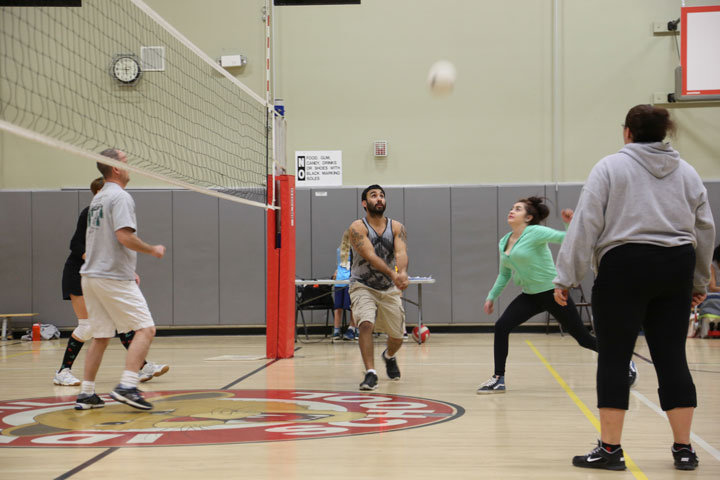 At right, during Friday's adult volleyball game, Frank Floanio returns the ball. Photo by Cheryl Basye