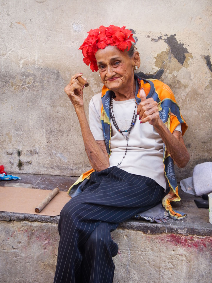 Rolling her cigar, looking fine and waiting for tips from passersby eager for a picture, an old woman in old Havana. Photo by Erin O'Neill