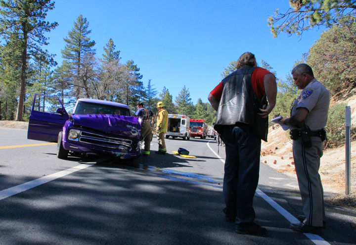 CLASSIC CAR CRASHES: James Dunn gives information to California Highway Patrol Officer Ron Esparza after father Robert Dunn of Idyllwild collided with an SUV Sunday morning on Highway 243 near the Nature Center. Jacob Murphy of San Clemente was driving a Toyota 4Runner on the Nature Center road at about 11:45 a.m. After stopping at the intersection to the highway, he reported that he looked and then turned left toward Pine Cove when he was struck by Dunn's classic purple Suburban traveling at 45 to 50 mph on Highway 243. Dunn's vehicle sustained major front-end damage. Murphy was uninjured but his passenger, Jocylin Fuentes, complained of pain to the left rib and was transported to Riverside County Regional Medical Center. Dunn was transported to Hemet Valley Medical Center for pain in his right knee. Photo by John Drake