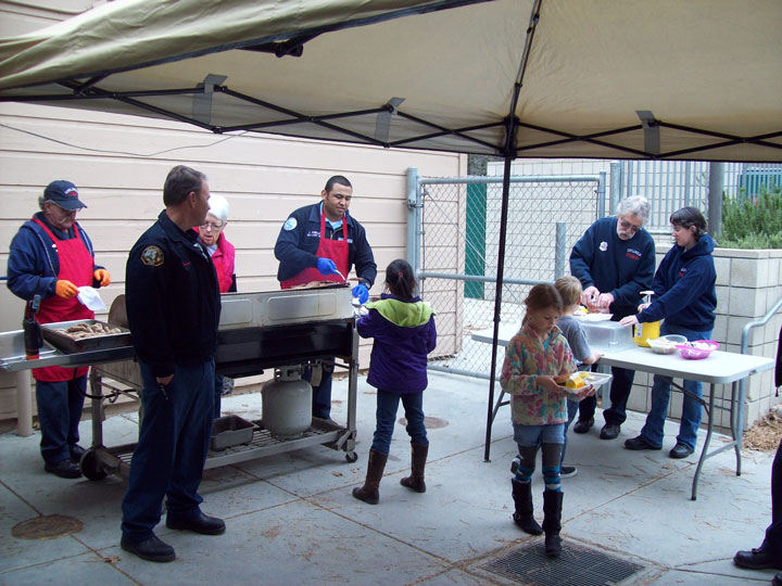 FIREFIGHTERS GRILL: Idyllwild firefighters and volunteer firefighters served up hamburgers for Sports Team Day last Thursday at Idyllwild School, in honor of the upcoming Super Kids Bowl and Super Bowl. Photo courtesy Bethany Swanson