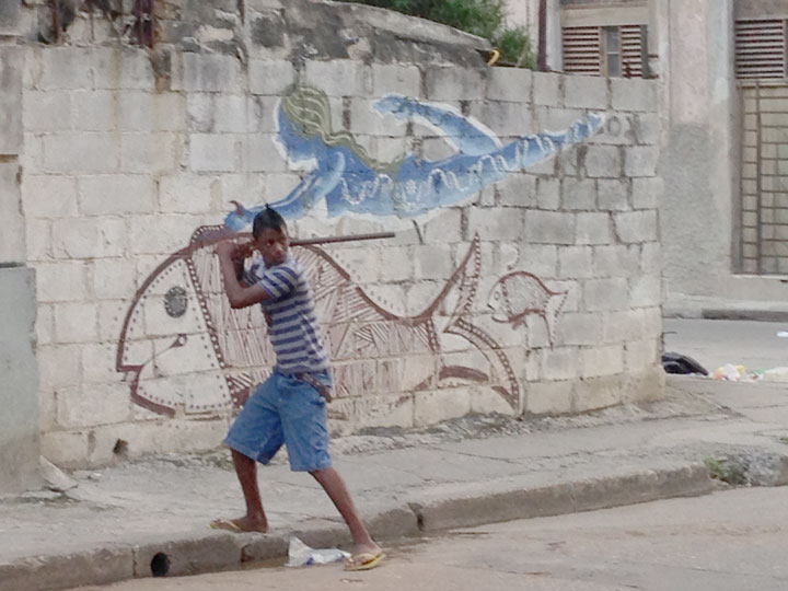 Baseball begins early in Cuba — a young boy on the street in Havana. Photo by George Companiott