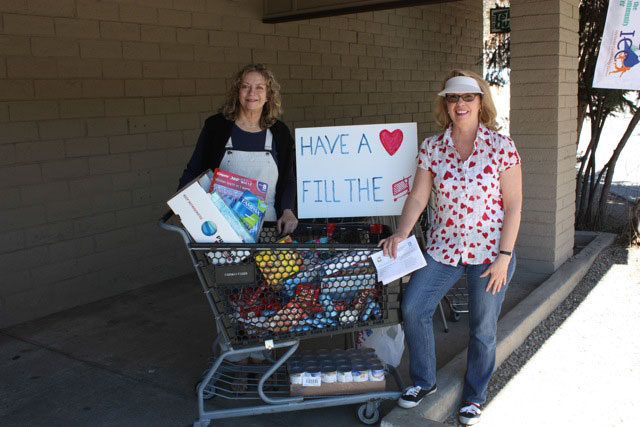 From left, Virginia Lumb and Tori Thomas, members of Soroptimist International of Idyllwild, help collect items for the Idyllwild HELP Center on Saturday's Soroptimist Day of Service. Emphasis was to collect items for the Soroptimist Women's Cabinet, a new project started in partnership with the HELP Center that supplies items needed for personal hygiene. More than 40 bags of food and hygiene items were purchased by community members and donated for the cause. Photo by Susan De Antonio