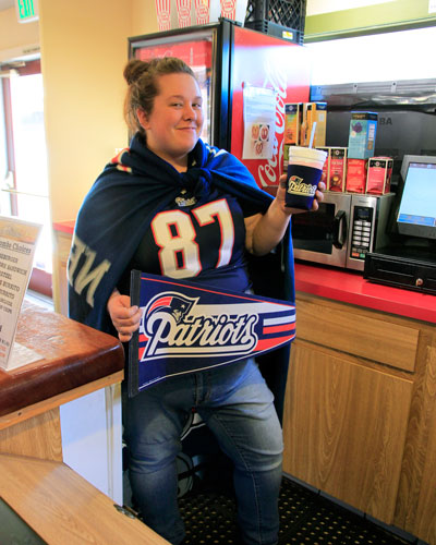 SUPERBOWL: Lauren Haynes, cashier at The Rustic Theatre and major Patriots fan, was adorned with a Patriots blanket, T-shirt, socks and purse, which she thinks contributed to their Super Bowl victory Sunday. The Rustic opened their doors for a free viewing of the game Sunday.