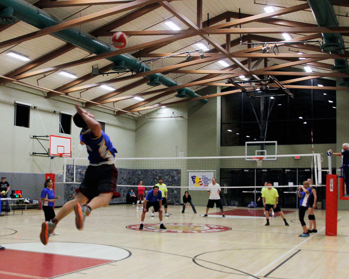 ADULT VOLLEYBALL CONTINUES: Idyllwild Garage, in blue, played Forest Lumber Monday night in adult volleyball. Here, Cory Sumerall of Idyllwild Garage serves to begin the third game with a spike across the net.Photo by John Drake