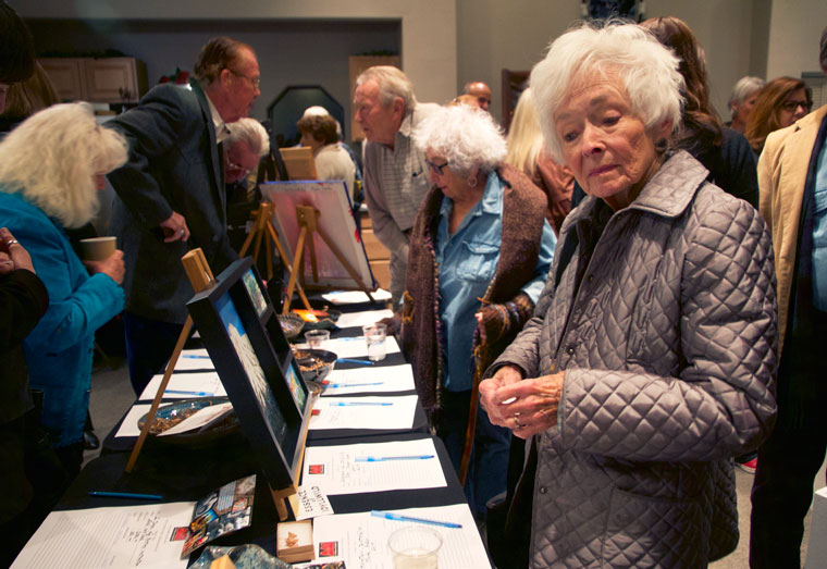 Sue Brackenbury visits from Colorado to attend AAI's most popular event. Other attendees enjoy the pieces of art available at the silent auction during the Art Alliance of Idyllwild's Eye of the Artist event at the Caine Learning Center on Saturday. Photos by John Drake