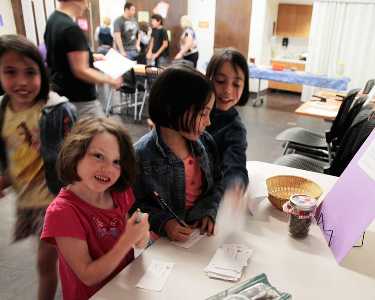 """Eryn Noble (left) and triplets Calista (back), Jossilin and Lorelei Nowell  get ready to guess how many milk balls are in the jar at Idyllwild Library's """"Pi day"""" on 3.14.15.Photo by John Drake"""
