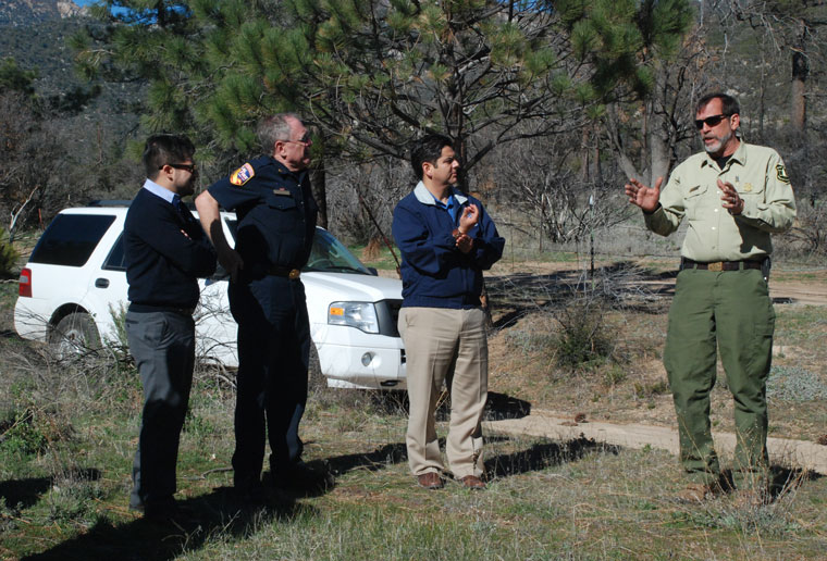 Dan Felix (right), San Jacinto Ranger District fire manager, discusses the Mountain Fire during a tour of the burned area Friday for Congressman Dr. Raul Ruiz (second from right). Also listening to Felix are Octavio Gonzalez (left), Ruiz's district policy director, and Riverside County Fire Chief John Hawkins (second from left). Photo by Jodie Hagemann, Riverside County Fire Department