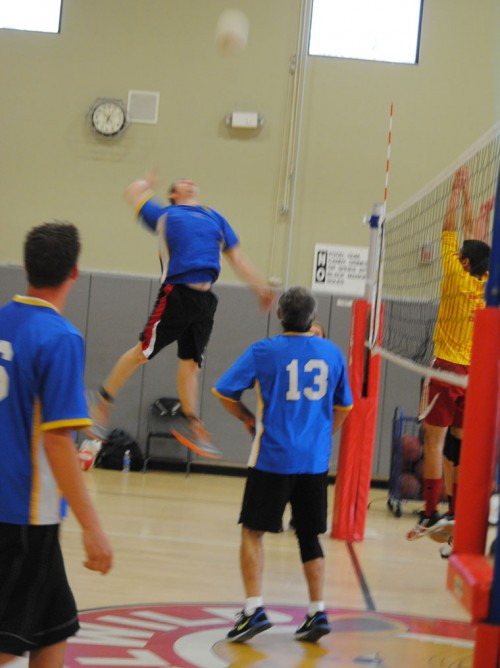 Corey Sumrall of Idyllwild Garage goes up for a spike during Saturday's Town Hall Adult Volleyball Championship. Garage won its fifth straight championship defeating Idyllwild Pizza Company. Teammates Kyle Owen and Art Torrez (13) watch Summrall earn the point. Photo by J.P. Crumrine
