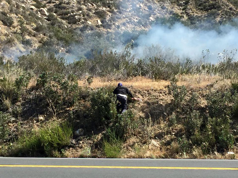 In this photo, Dan Crabtree of Idyllwild Garage is seen climbing up the hillside before attempting to fire-extinguish the Cranston Fire before firefighters arrived on Tuesday, April 7.Photo by Marjie Ibanez