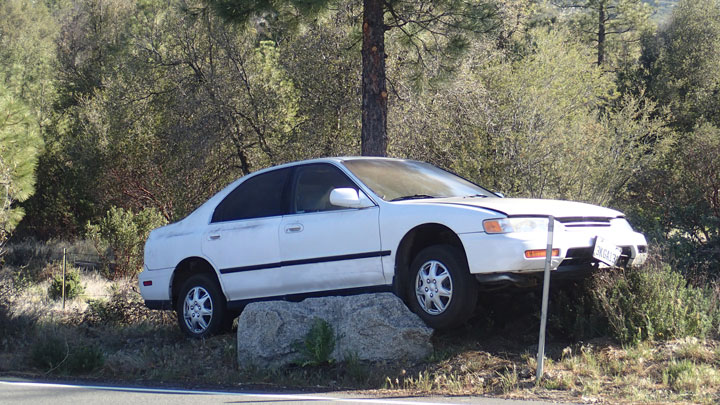 """""""An interesting parking job,"""" noted California Highway Patrol Public Information Officer Darren Meyer when shown this photo for identification purposes. Idyllwild Garage towed the car from Highway 243 in Mountain Center near Gibraltar Ranch Monday morning to the owner's home in Idyllwild after it had come to rest on its rock perch the night before. CHP was not called to respond and no further details were available. Photo by Halie Wilson"""
