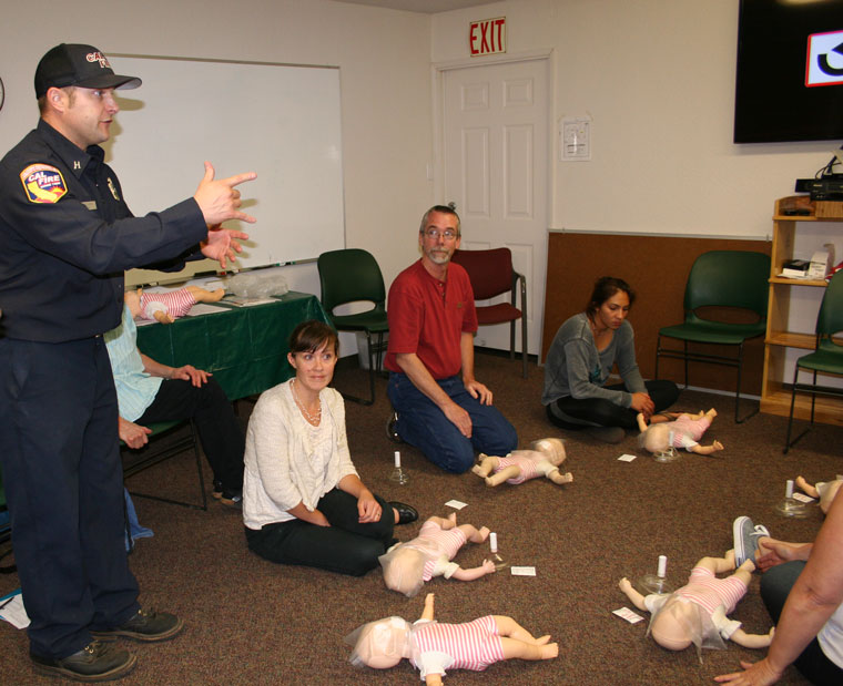 Pine Cove Station 23 Capt. Tim Ellena teaches a free CPR class at the Mountain Resource Center Wednesday evening, May 27. Shown practicing on the floor are, from left, Halie Wilson and Mile High Radio Club President Bill Tell. Riverside County Fire teaches the class in conjunction with the American Heart Association. The free class covers infants to adults and also choking cases.Photo by Becky Clark