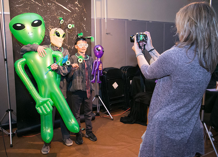Kirsten Ingbretsen's (right) photo booth with alien props was a big hit at the middle-school dance.