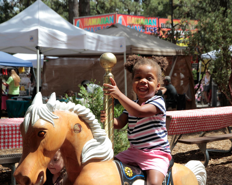 Emmerson Renner enjoys herself on the wooden horses at the Lemon Lily Festival over the weekend.   Photo by John Drake