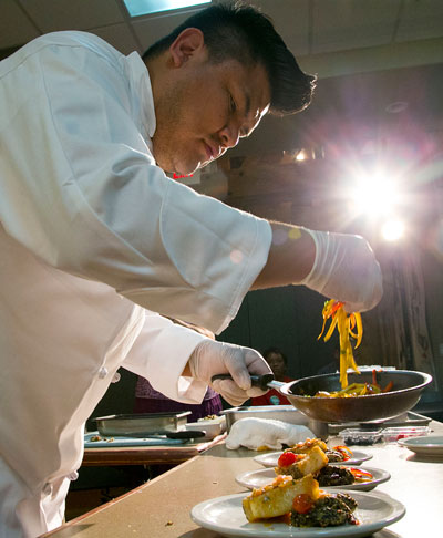 Chef Freddie Bitsoie, from the Navajo tribe, starts plating his entree as time runs out during the Native American Chef Competition Friday night at Idyllwild Arts. Photo by Jenny Kirchner