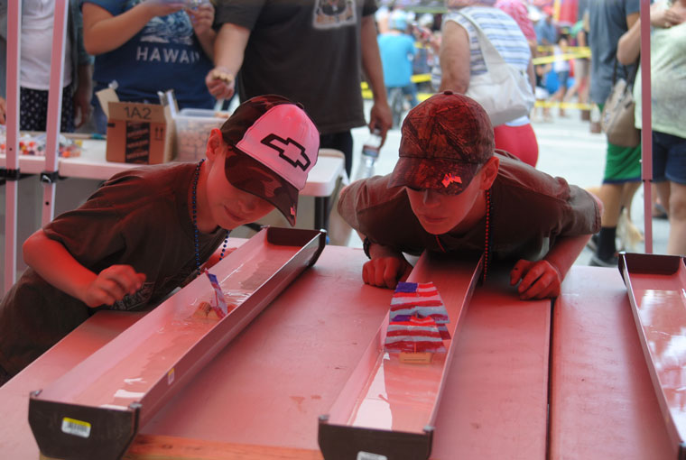 From left, Devin Zigmont and Caleb Zigmont race their boats during the Rotary's Fourth of July Festival after the parade downtown. The boys were helping Grandmother Janice Murasko raise money at the booth for the Animal Rescue Friends of Idyllwild. Photo by J.P. Crumrine