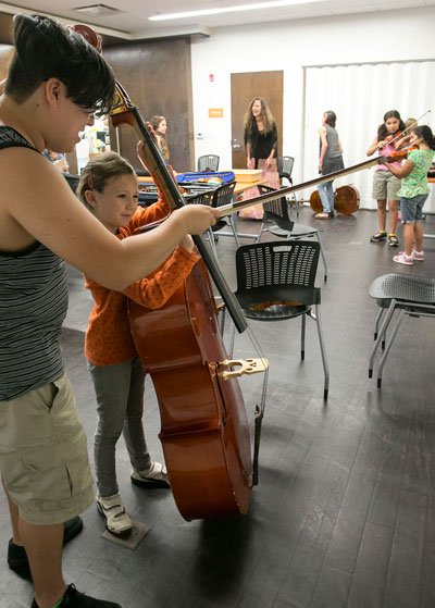"Robert Carcano (left) teaches Briar Scott, 8, about the upright bass during the ""Instrument Petting Zoo"" event at the Idyllwild Library Tuesday afternoon, June 30. Photo by Jenny Kirchner"