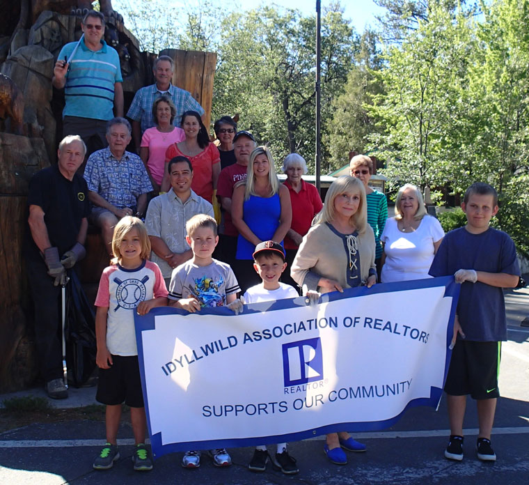 Members of the Idyllwild Association of Realtors conducted a town cleanup in the morning of Tuesday, July 7, following the busy holiday weekend. Volunteers shown here are (from left, front holding sign) Griffin Kretsinger, Hunter Stewart, Zane Booth, Christina Stewart and Dillon Stewart; (from left, second row) Johnny Wilson, Amber Booth, Marge Muir, Trischa Clark and Jackie Kretsinger; (from left, third row) Jim Billman, Jim Palmer, Dora Dillman, Shelly McKay, Barbara Hunt and Joe McNabb; and (from left, top) Wayne Johnston and Chris Davis. The cleanup netted some 15 bags of trash. Photo by Halie Wilson