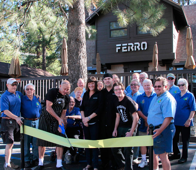 Surrounded by Rotarians from Idyllwild's Rotary Club, Frank Ferro holds the scissors for the ribbon cutting. Accompanying him from Ferro are (from left) wife and co-owner Lori Ferro, Chef Geoff Brown and Justin Holmes. They cut the ribbon to hail the opening of Ferro Restaurant on Monday morning. Rotarians are, from left, Chuck Weisbart, Earl Parker, Charlie Wix (seated), Cathy Duncan, Chuck Streeter, Jeffrey Cohen, Steve Espinosa, Craig Coopersmith, Danny Richardson and John Graham.Back row, from left behind Coopermith, Chris Scott, Scott Fisher Thom Wallace and Reba Coulter. Photo by John Drake