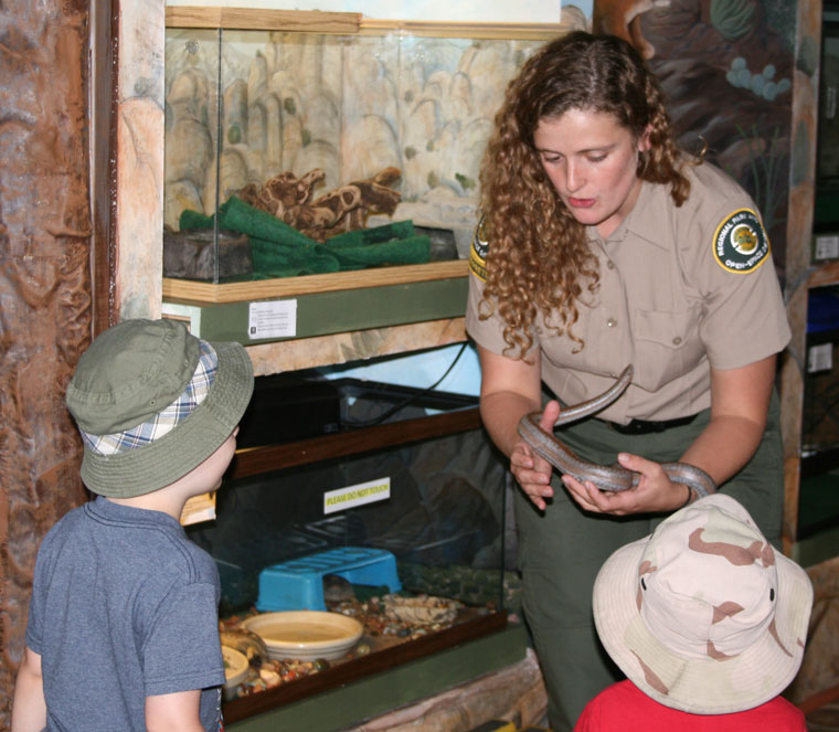 Amanda Allen, new Nature Center park interpreter, is shown introducing center resident gopher snake Elvis to two young off-Hill visitors. Photo by Marshall Smith