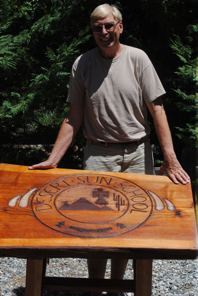 """Ronn Rohe of San Diego and alumnus of the Desert Sun School, donated this sign, now a table, to the Idyllwild Area Historical Society. It hung at the entrance to Desert Sun School (now AstroCamp) from 1946 though 1983, when it became the Elliott Pope Preparatory School. """"At a school reunion in 2014, IAHS Director Robert Smith accepted donations of other DSS memorabilia and indicated that the museum """"could really use a table. With that, the 14-square-foot sign, hand-carved from a solid cut of pine, was re-purposed into functional furniture,"""" Rohe said.Photo by JP Crumrine"""