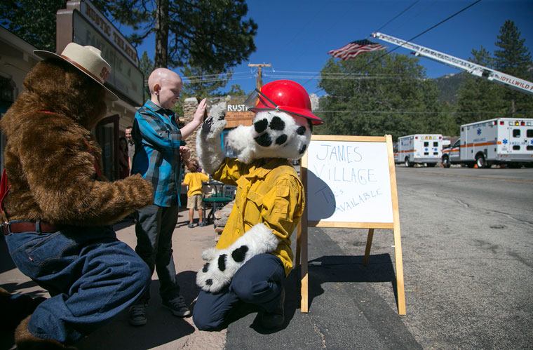 "James Bachmann, 12, of Idyllwild, has medulloblastoma, a brain cancer. Here he poses with Smokey and Sparky after arriving to a fundraiser, ""James' Village,"" which was held at the Rustic Theatre Friday afternoon and evening, Aug. 21, to help raise funds for his medical bills. Photo by Jenny Kirchner"