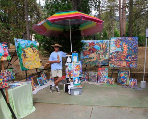 At Saturday's Second Saturday Art Fair, Rob Padilla stands among his art, some depicting life in Idyllwild.Photo by John Drake