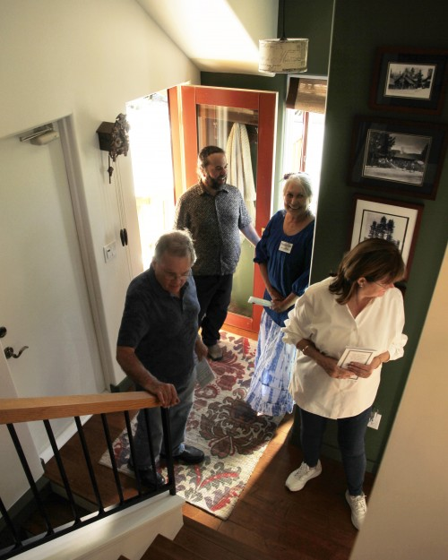 At one of the homes on the 15th-annual Idyllwild Home Tour, which the Idyllwild Area Historical Society sponsors, IAHS docent Pamela Fojtik (center) welcomes old Idyllwild friends Evan Mills (entering) and Charles and Carol Russell. Photo by John Drake
