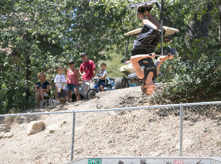 Jeremy Trogdon, 18, of Hemet, does a back flip on his scooter during the scooter portion of the contest, as supporters watch on from above the skate park. The Idyllwild Assembly of God sponsored the Skate Boarding Bash 2015 Saturday. Photo by Jenny Kirchner