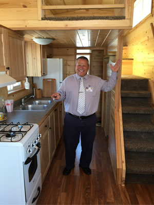 """Scott Sirois, Soboba Casino general manager, is pictured here inside and with the key to the tiny home that will be given away this September in the casino's promotion """"Tiny Home, Giant Free Play."""" The grand prize is a tiny home built by Rich's Portable Cabins and that will be featured in an upcoming episode of HGTV's program """"Tiny House Hunters."""" Photo courtesy Soboba Casino"""