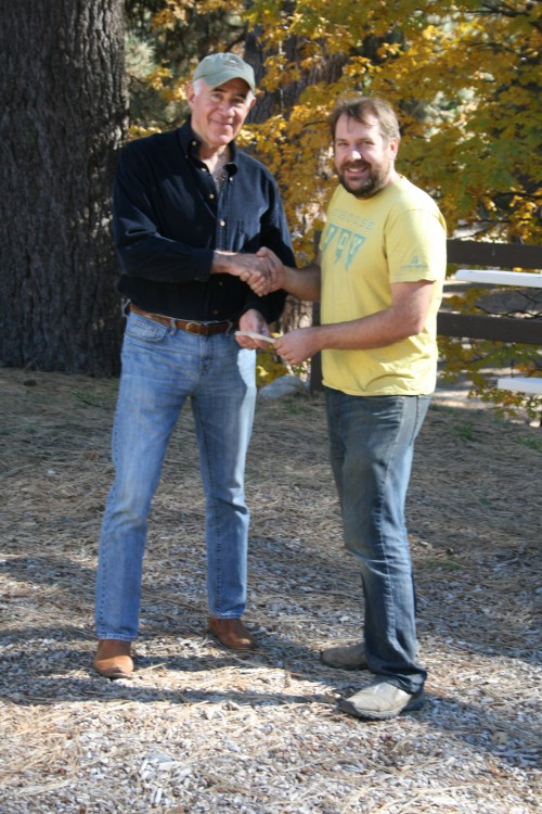 Dr. Dick Goldberg, Mountain Disaster Preparedness medical director (left) shakes hands with Kelly Schlenz, Idyllwild Pines Camp director of operations, upon reaching an agreement for Idyllwild Pines to provide campus space at McNeil Hall, the largest camp facility, for use by MDP as a medical center following a disaster. Goldberg also gave Schlenz a check for a fundraiser Schlenz was conducting in appreciation for the camp's outreach to MDP and the community. Photo by Marshall Smith
