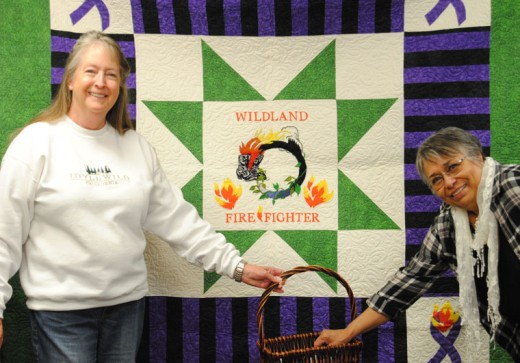 Katie Holldber (left) holds a basketful of tickets from which Dolores Sizer (right) pulled Elizabeth Vargas' name. She is the wife of a Vista Grande Hot Shot. Sue Draper of Pine Cove sewed the quilt, and Holldber raised $1,700 through raffle tickets. The funds will go the Wildland Firefighter Foundation in Boise, Idaho. Photo by JP Crumrine