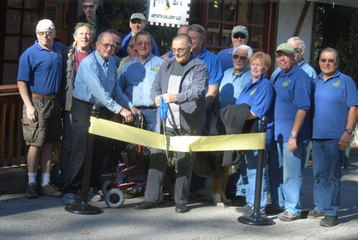 On Monday, Nov. 2, Jerry Baccaire, owner of Jerry Art, cuts the Rotary ribbon in anticipation of the grand opening later that week. Rotary members participating in the ribbon cutting are Charlie Wix, next to Baccaire, and (in the first row, from left) Chuck Weisbart, Dennis Dunbare, John Graham, Craig Coopersmith, Ric Foster, Christopher Scott, Earl Parker, Kathy Duncan, Jefrey Cohen and Steve Espinosa. (Back row, from left) are Roland Gaebert, Eric Gaebert, Chuck Streeter (behind Scott), Thom Wallace and Terry Kurr.Photo by JP Crumrine