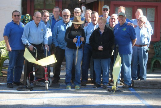 Cat Orlando (center), owner of Mountain Boho, where you find eclectic handmade treasures, cuts the Rotary ribbon. Rotarians at the cutting were (from left) Steve Espinosa, Charlie Wix, John Graham, Roland Gaebert, Terry Kurr, Chuck Weisbart, Dennis Dunbare, Ric Foster, Kathy Duncan, Thom Wallace, Craig Coopersmith, Christopher Scott, Jeffrey Cohen, Chuck Streeter and Earl Parker. Photo by JP Crumrine