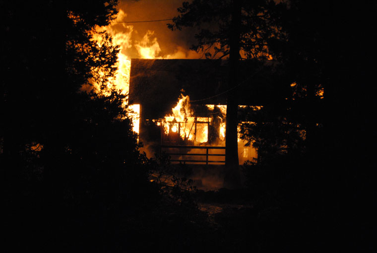 The house at 25435 Scenic Drive burned Sunday night. Idyllwild Fire Department, with mutual aid from neighboring stations and the rain, extinguished the fire before it spread to the nearby trees. Photo by JP Crumrine