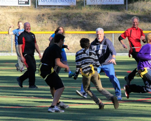 Students Chayton Kenyon and Jeremiah Whitney charge teacher George Campaniott (center) during the annual Idyllwild Middle School Turkey Bowl. Principal Matt Kraemer (left) chuckles and teacher Bob Leih (right) watches the play develop. Photo by John Drake