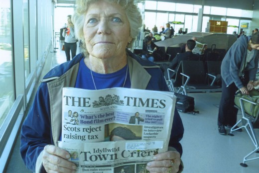 Janet Reynolds of Idyllwild displaying the Town Crier along with the Scotland Times in the Edinburgh airport before departing home to the U.S. after a tour of the seven cathedrals in Europe built on pre-neolithic sites. These included St. James in Compostela, Spain; Notre-Dame de la Dalbade, Orleans Cathedral, Chartres Cathedral, Notre-Dame de Paris, Åmiens Cathedral, all in France; and Rosslyn Chapel in Scotland. Photo courtesy Janet Reynolds