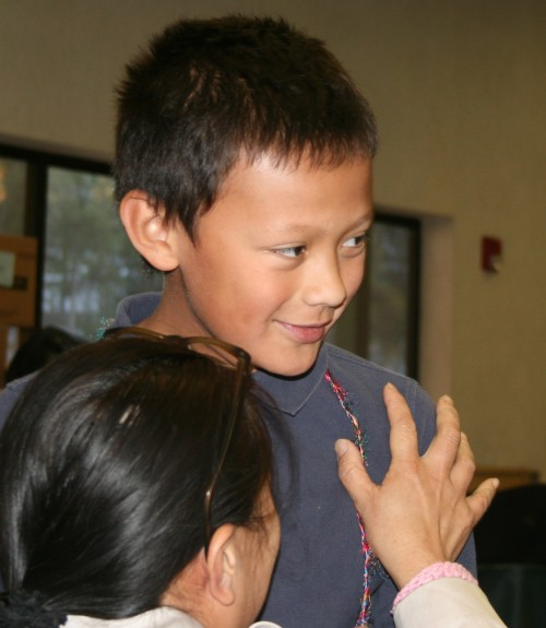 Idyllwild Elementary School Spelling Bee champion Michael Stroud receives a congratulatory hug from his mother, Anne Stroud. Michael, fifth grade, and his sister, Mei Li, fourth grade, were first and second respectively in the Elementary School section of the Bee. Jessica Ruelas and Grace McKimson, both sixth grade, were first and second respectively in the Middle School section. All four will represent Idyllwild School at the Hemet Unified School District Spelling Bee in January. Photo by Marshall Smith