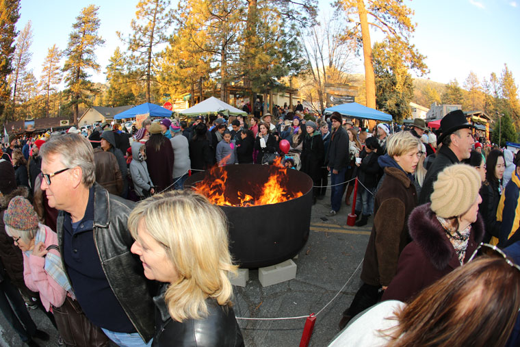 Despite the cold temperatures Saturday, the throng attending the Tree Lighting Ceremony warm themselves next to the fire, which Rob Muir and his mother Marge lit.